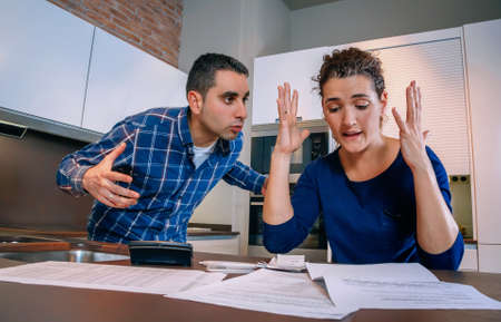 Angry young couple shouting in a hard quarrel by their many debts at home. Financial family problems concept.