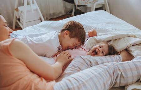 Vértes boldog családi játék az ágy fölé egy nyugodt reggel. Hétvégi családi szabadidő fogalma. Stock fotó