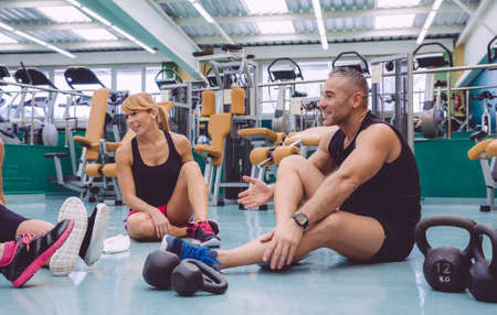 personal trainer: Couple talking with friends sitting on the floor of a fitness center after hard training day Stock Photo