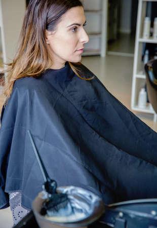 tinte cabello: Hermosa mujer joven listo para un cambio de color de cabello con tinte para el cabello desenfocado en un tazón y cepillo en el primer plano