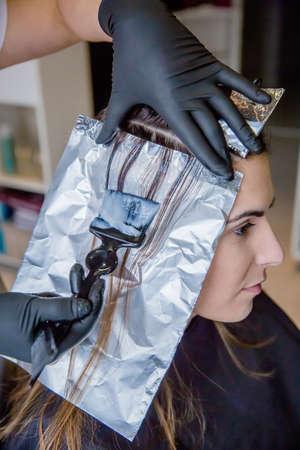 tinte cabello: Primer plano de las manos del peluquero aplicando tinte para el cabello de la mujer hermosa joven en un salón de peluquería y belleza Foto de archivo