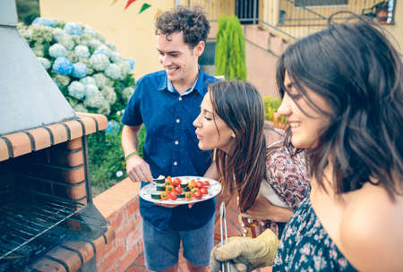 garden parties: Group of young friends cooking vegetable skewers and having fun in a outdoors summer barbecue