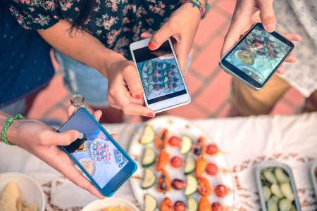 야외에서 여름 바베큐 테이블 위로 야채 꼬치에 자신의 스마트 폰으로 사진을 찍고 젊은 친구 손의 근접 촬영 스톡 콘텐츠