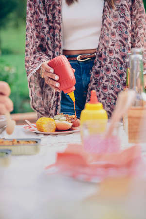 one dog: Closeup of woman hand pouring ketchup over an american hot dog in a outdoors summer barbecue