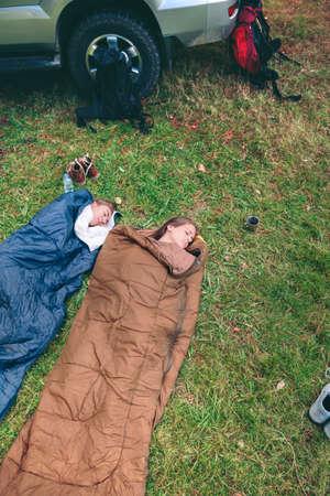 gente durmiendo: Vista superior de jóvenes hermosas mujeres amigos que duermen en la naturaleza en el interior de los sacos de dormir con sus mochilas y vehículos 4x4 en el fondo