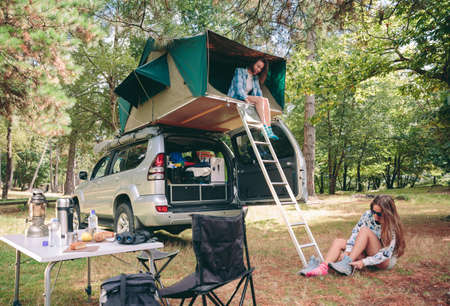 Young happy woman resting in a tent on the roof of 4x4 while other woman putting hiking boots sitting on the grass