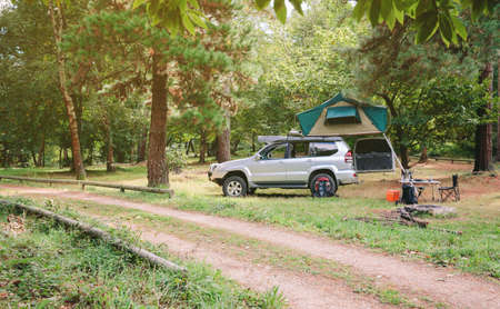 Landscape of 4x4 offroad vehicle with tent in the roof ready for camping next to dirt road with the forest in the background