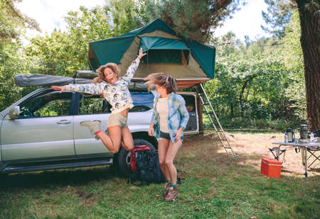 boot camp: Young beautiful women friends having fun in a campsite with their 4x4 vehicle with tent in the roof on the background