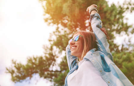 freedom nature: View from below of young beautiful happy woman with sunglasses and blue plaid shirt raising her arms over a sky and trees background. Freedom and enjoy concept. Stock Photo