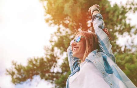 Vista dal basso di giovane e bella donna felice con occhiali da sole e camicia blu a quadri, alzando le braccia su un fondo cielo e gli alberi. Libertà e godere concept.
