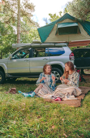 shoes off: Happy young women friends resting sitting under a blanket and their 4x4 vehicle with tent in the roof on the background
