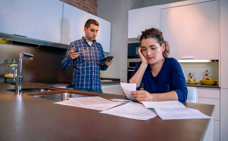 Wanhopige jonge paar met veel schulden herziening van hun rekeningen. Financiële familiale problemen concept. Stockfoto