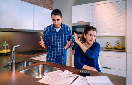 problemas familiares: Marido joven que intenta reconciliarse con su esposa enojada despu�s de una pelea por sus muchas deudas en casa. Concepto financiero de los problemas familiares. Foto de archivo