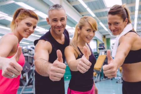 gente exitosa: Grupo de amigos con los pulgares para arriba sonriendo en un gimnasio después de días de entrenamiento duro. Selectivo se centran en las manos.