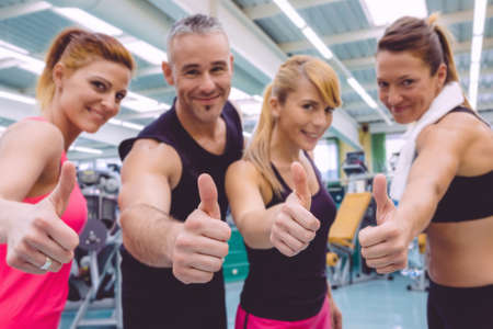 Group of friends with thumbs up smiling on a fitness center after hard training day. Selective focus on hands. Archivio Fotografico