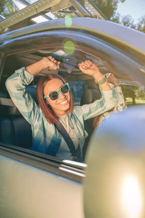 Portrait of happy young woman raising her arms and having fun inside of car in a road trip adventure. Female friendship and leisure time concept. Standard-Bild