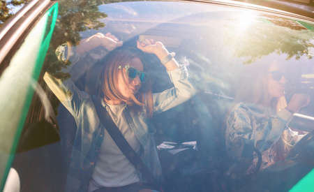 Two happy young women friends with sunglasses dancing and having fun inside of car in a road trip adventure. Female friendship and leisure time concept.