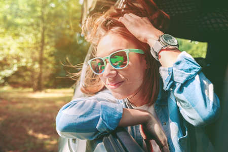 drive car: Portrait of happy young woman with sunglasses looking through the window car in a sunny day