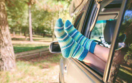 legs open: Closeup of female legs with blue striped socks resting over a open window car over a nature background. Travel and relax time concept. Stock Photo