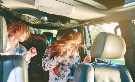 leisure time: Two happy young women friends dancing and having fun inside of car in a road trip adventure. Female friendship and leisure time concept. Note: Women heads are in motion.