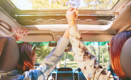 front raise: Back view of happy young women friends holding hands and raising their arms inside of car in a road trip adventure. Female friendship and leisure time concept. Stock Photo
