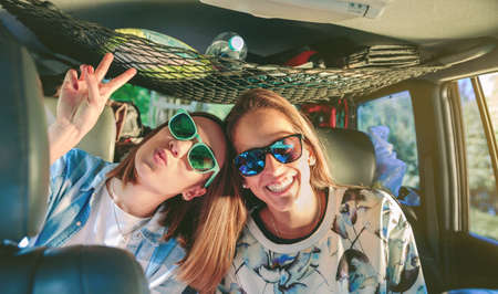 love and friendship: Two happy young women friends with sunglasses laughing and having fun inside of car in a road trip adventure. Female friendship and leisure time concept.