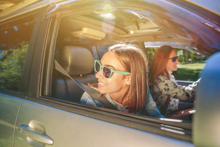 Portrait of happy young woman looking back through the window car while her friend driving in a road trip adventure. Female friendship and leisure time concept.