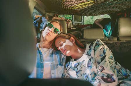 두 피곤 된 젊은 여자 친구가 함께 자동차의 뒷자리에 자. 여성 우정과 여가 시간 개념입니다. 스톡 콘텐츠