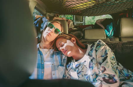 Two tired young women friends sleeping together in the rear seat of car. Female friendship and leisure time concept.