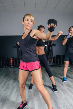 kickboxing: Group of people in a hard boxing class on gym training punch