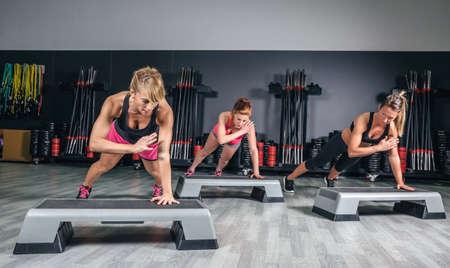gimnasio mujeres: Grupo de mujeres entrenando duro durante steppers en clase de aeróbicos en un gimnasio. El deporte y el concepto de salud. Foto de archivo
