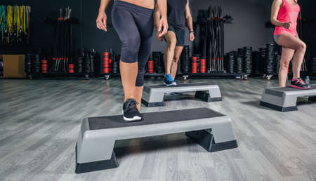 step fitness: Closeup of people legs over step boards training in aerobic class on a fitness center. Sport and health concept.