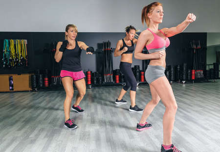 boxing sport: Group of beautiful women in a hard boxing class on gym training punch