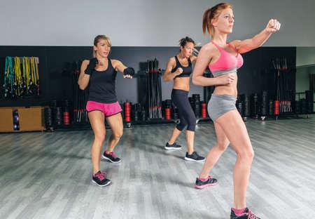 Grupo de mulheres bonitas em uma classe de boxe duro no treinamento da ginástica soco Imagens