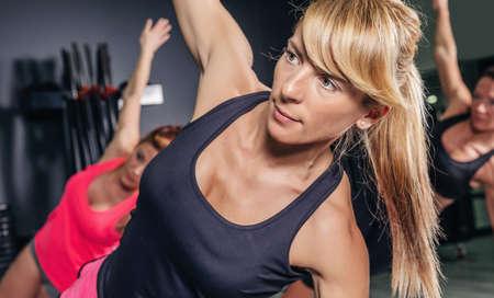 gimnasia aerobica: Detalle de mujer haciendo ejercicios en clase de aer�bicos con un grupo en un gimnasio. El deporte y el concepto de salud.