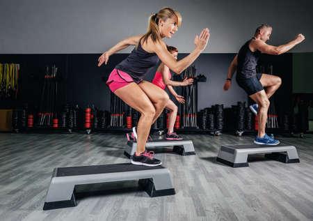Athletic kvinna tränare gör aerob klass med steppers till människor grupp på ett fitnesscenter. Idrott och hälsa koncept.