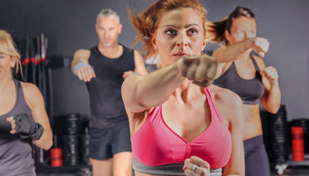 Group of people in a hard boxing class on gym training punch