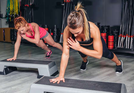 Closeup of women couple training hard over steppers in aerobic class on a fitness center. Sport and health concept. Stock Photo