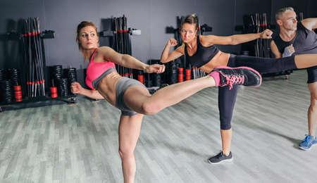Grupo de pessoas em uma classe de boxe duro no ginásio formação chute alto