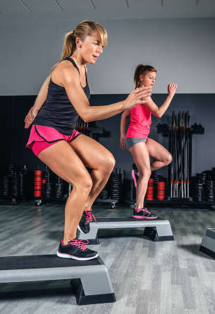 Women couple training hard over steppers in aerobic class on a fitness center. Sport and health concept.