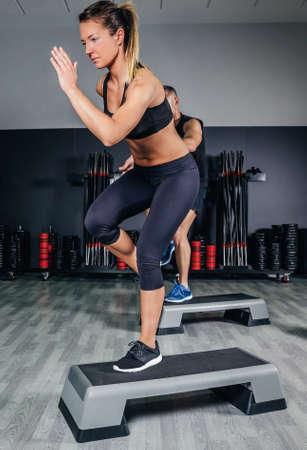 gimnasia aerobica: Atlético pareja haciendo ejercicios sobre pasos en clase de aeróbicos en un gimnasio. El deporte y el concepto de salud.