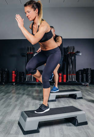 Athletic couple doing exercises over steps in aerobic class on a fitness center. Sport and health concept. Stockfoto
