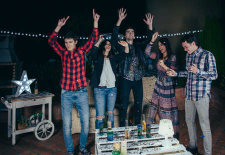 man drinking beer: Group of happy young friends dancing and having fun with the music in a outdoors party. Friendship and celebrations concept. Stock Photo