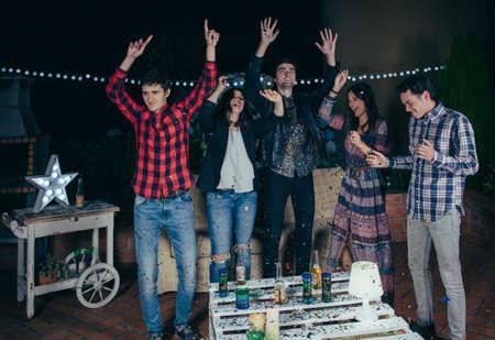 hombre tomando cerveza: Grupo de jóvenes amigos felices bailando y divirtiéndose con la música en una fiesta al aire libre. Concepto de la amistad y las celebraciones.