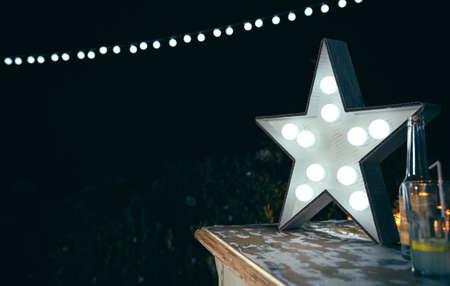 야외 파티에서 백그라운드로 음료와 조명 갈 랜드와 함께 나무 테이블 위에 전구 흰색 수제 스타 램프의 근접 촬영 스톡 콘텐츠