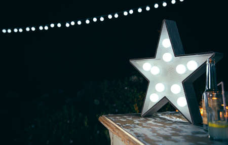 Closeup of white handmade star lamp with light bulbs over a wooden table with drinks and lights garland in the background in a outdoors party