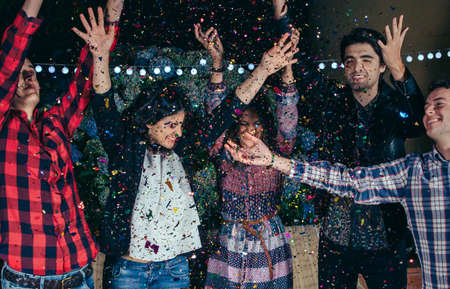 confetti: Closeup of happy young friends raising their arms and having fun among the colorful confetti cloud in a outdoors party. Friendship and celebrations concept. Stock Photo