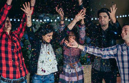 Mutlu genç arkadaşlar kollarını yükselterek ve bir açık parti renkli konfeti bulut arasındaki eğlenmenin çekim. Arkadaşlık ve kutlamalar kavramı. Stok Fotoğraf