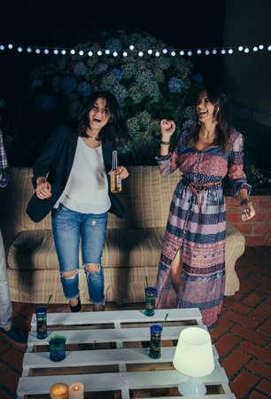 gente bailando: Feliz de dos mujeres jóvenes amigos a bailar y divertirse en una fiesta al aire libre. Concepto de la amistad y las celebraciones.
