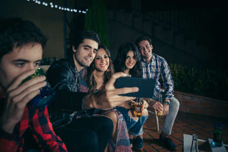 party night: Group of happy young friends drinking and taking a selfie photo with smartphone in a outdoors party. Friendship and celebrations concept. Stock Photo